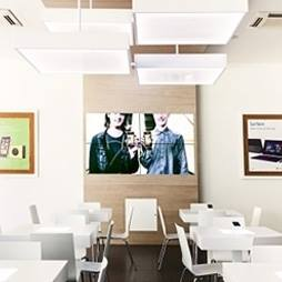 stanza con delle piccole scrivanie e sedie bianche e al centro un pannello illustrante due persone su uno specchio a Segrate, MI