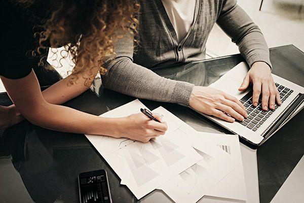 un uomo e una donna con fogli e laptop
