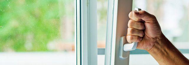 Mano maschile sta aprendo una finestra in alluminio a Montemurlo