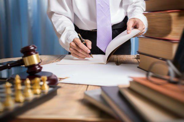 Uomo firmando un documento, accanto libri,scacchi e un mazzo di giustizia