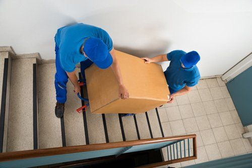 Two professionals carrying big box by stairs