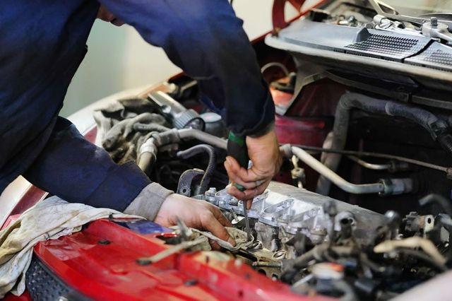 un meccanico con un cacciavite ripara un motore
