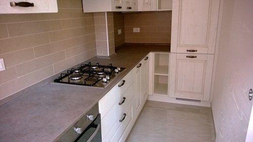 Una cucina angolare con mobili bianchi e top in marmo