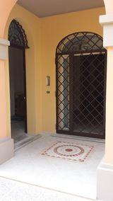 Un patio con un pavimento in marmo con un disegno e un'inferriata a una porta finestra