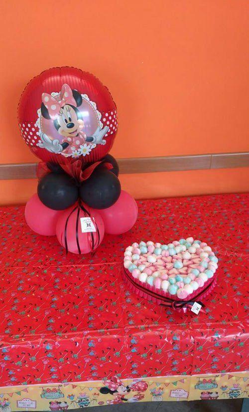 Dei palloncini rossi e neri con il disegno di Minnie e dei confetti disposti in modo tale da formare un cuore