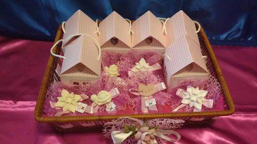 Delle bomboniere a forma di casetta e altre con dei veli viola