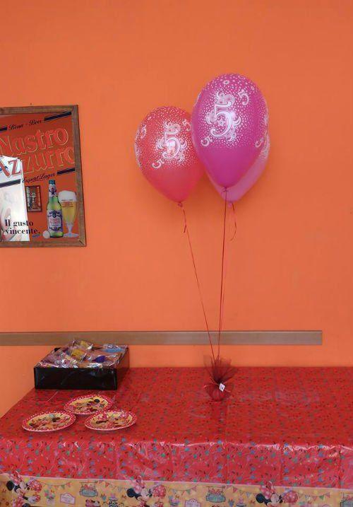 Un tavolo con una tovaglia rossa e dei palloncini viola e rossi