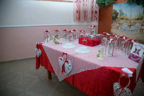 Un tavolo apparecchiato con una tovaglia rossa, un centrino in pizzo e delle bomboniere a forma di ombrellini