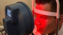 ragazzo con volto appoggiato allo strumento per la misurazione della vista