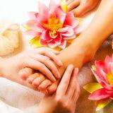 due mani che tengono un piede e accanto dei fiori