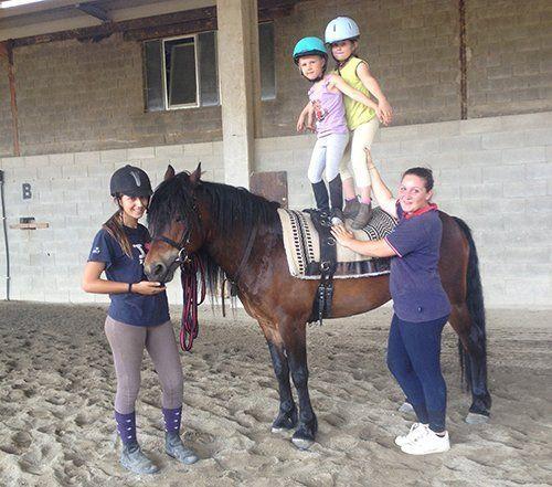 due bambini in piedi su un cavallo