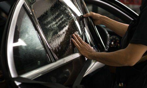 due mani appoggiate su un vetro di una macchina