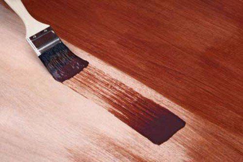 un pennello che tinge una superficie in legno di marrone
