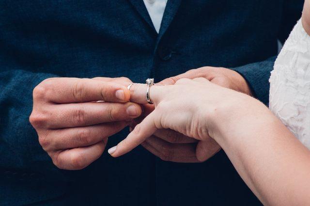 Primo piano mani di giovani sposi che si scambiano le fedi nuziali