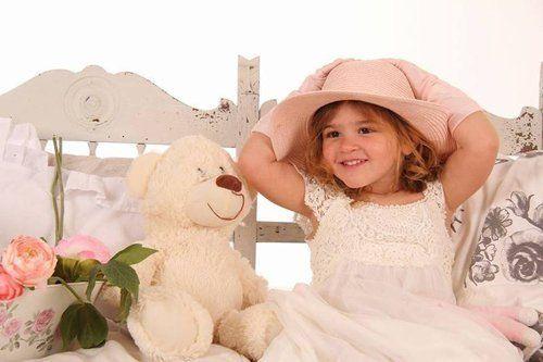 bambina seduta con cappello di fianco al suo orsetto