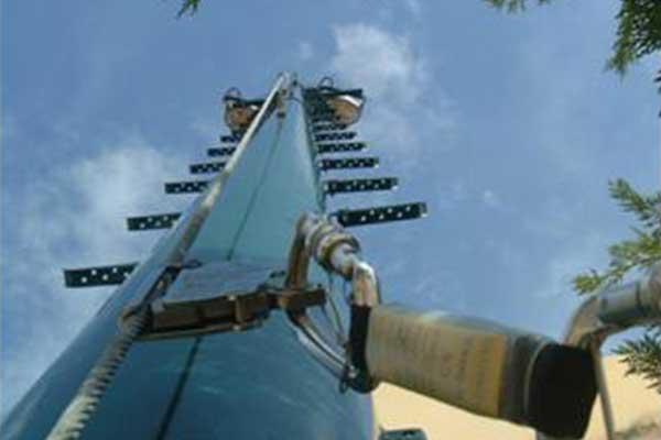 vista dal basso verso l'alto di un palo in ferro con un cavo d'acciaio e sulla destra un gancio