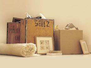A rolled up rug and pictures around crates and packing boxes