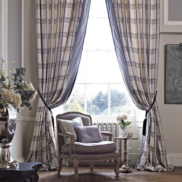 Curtains framing a window with a chair and cushions in front
