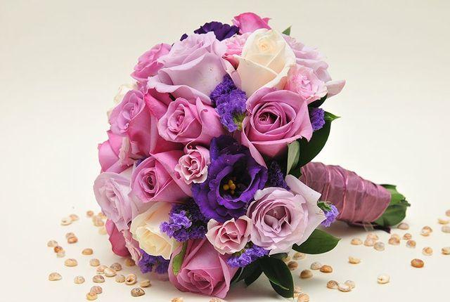 un bouquet di fiori di color rosa e lilla legati con un nastro di color lilla