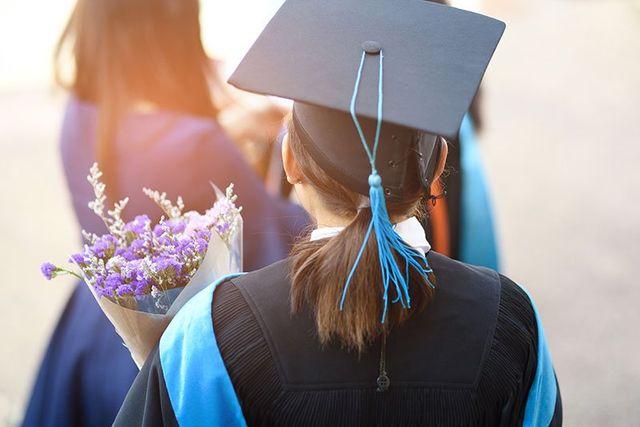 Una donna vista dal dietro  con un bouquet di fiori viola e bianchi