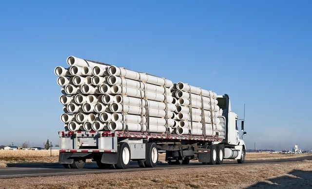 Big truck with flatbed trailer hauling plastic pipe
