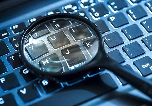 Lente di ingrandimento sul tastiera di un computer portatile,cercando tracce