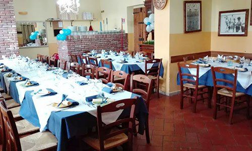 sala interna di un ristorante con lunghe tavolate e molte sedie