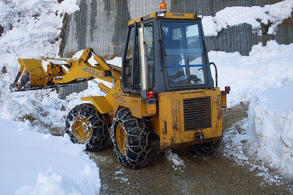 escavatore in azione ripulendo una strada dalla neve