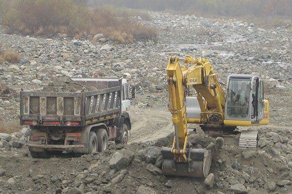 escavatore ed un camion trasporta massi