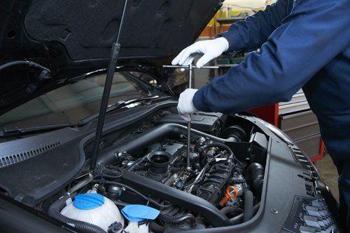 meccanico avvita le componenti di un motore esposto