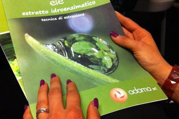 Due mani di donna che stanno per aprire una brochure Adama sull'estrazione idroenzimatica