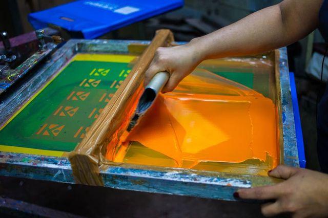 Comunicati stampa serigrafica con vernice arancione. Stampa schermo