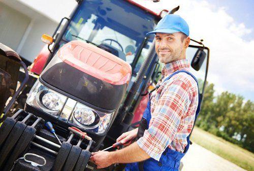 Operaio mentre ripara motore di un trattore agricolo
