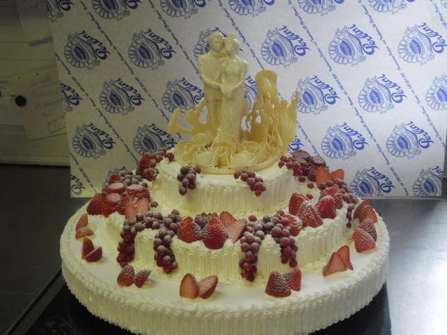 Torta nuziale di tre piani decorata con fragole e frutti rossi con la figura della coppia in cioccolato bianco