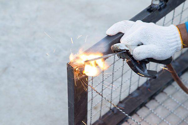 una mano con un guanto che usa una fiamma ossidrica sull'angolo di un telaio di ferro