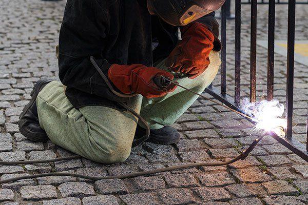 un uomo chinato a terra mentre utilizza una fiamma ossidrica