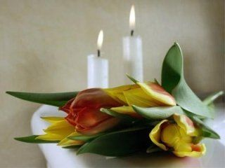 fiori sopra una bara con candele accese