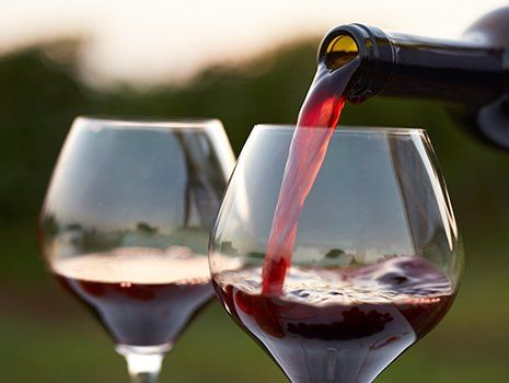 Due bicchieri di vino rossa e una bottiglia che sta versando