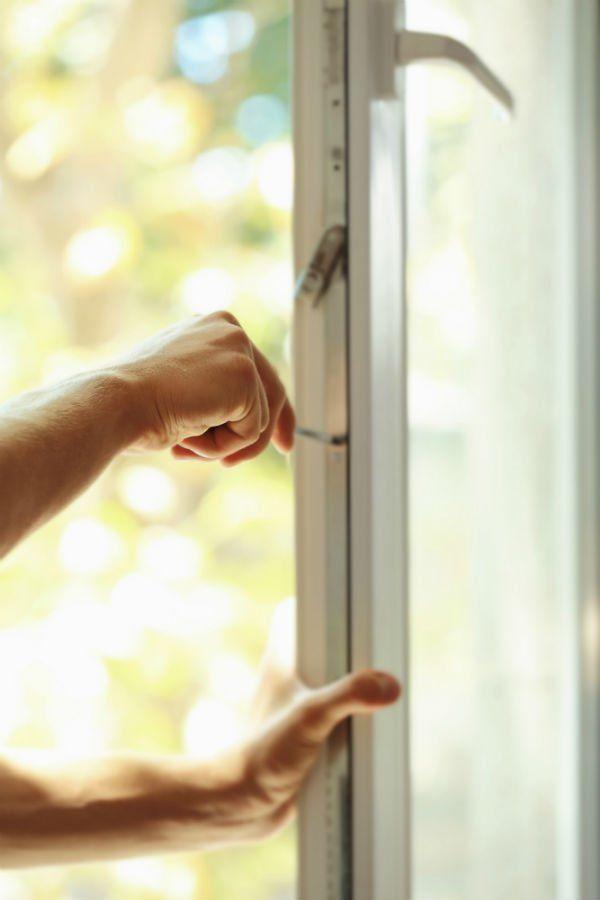 una mano con un cacciavite che sistema un'anta di una finestra