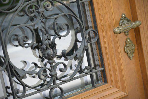 una porta in legno con finiture in ferro battuto al centro
