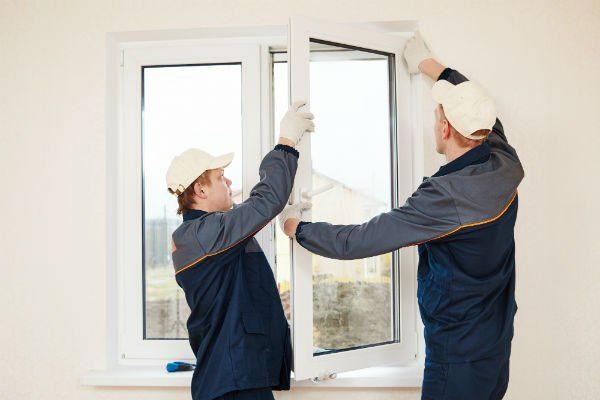 due operai che montano un' anta di una finestra in PVC