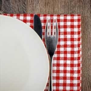 Vista parziale di piatto, forchetta e tovaglia
