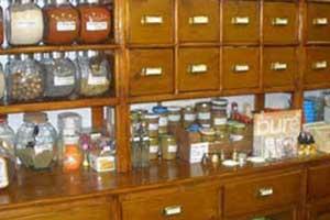 Interno del negozio, parete coperta di cassetti di legno e vasetti di vetro di diverse dimensioni