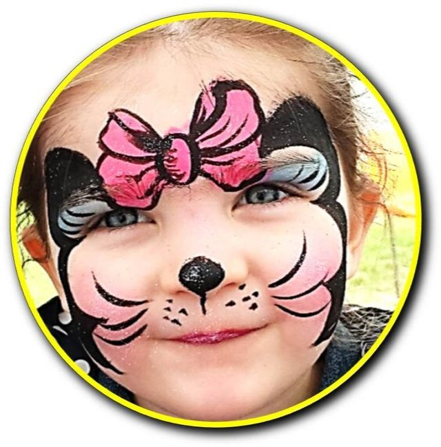 Girl's face painted with a cat with a bow