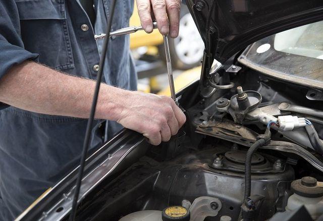 un meccanico con un cacciavite a T che svita un bullone nella zona motore di una macchina