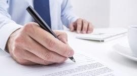 uomo in cravatta scrive su un documento