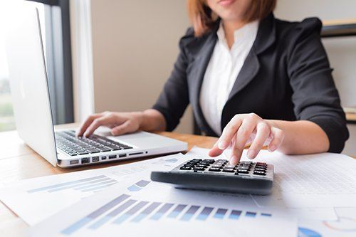 donna scrive al computer mentre da dei conti con una calcolatrice