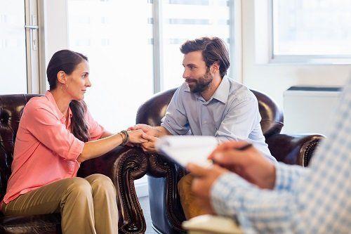 una coppia seduta che si tiene per mano e di fronte uno psicologo
