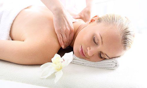 Therapeutic massage, heals the pain and relaxes. Attractive blonde woman in the office spa, relax with a massage
