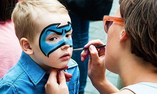 Woman painting face of kid